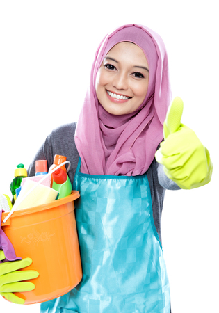 servicio domestico: cerca retrato de ama de casa hiyab celebración cubo lleno de productos de limpieza y dando pulgar hacia arriba aislados en blanco