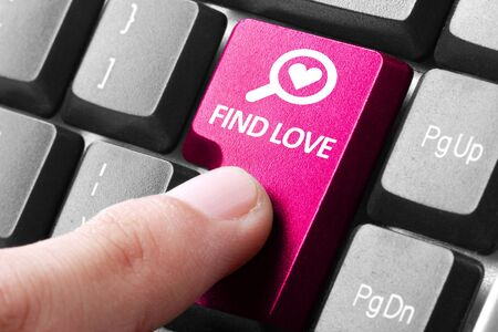matchmaking: looking for a couple. gesture of finger pressing find love button on a computer keyboard Stock Photo
