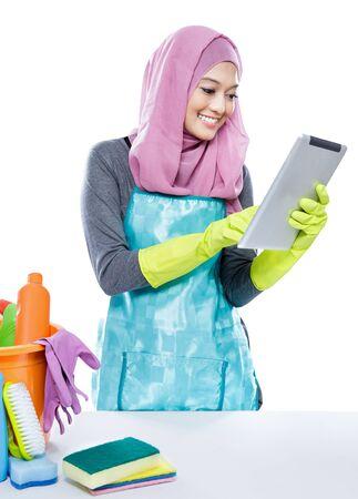 mandil: retrato de la multitarea joven ama de casa que usa la tableta mientras se limpia una mesa aislada en blanco Foto de archivo