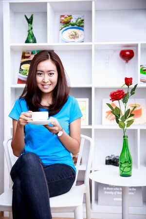livingroom: portrait of beautiful young woman sitting at decorated livingroom while enjoying a cup of tea Stock Photo