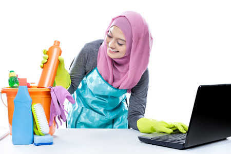 'pick up': portrait of multitasking housewife using laptop while pick up a bottle of cleaner isolated on white Stock Photo