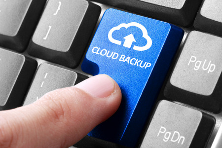 Back-up online via cloud. Gebaar van de vinger drukt wolk back-up knop op een computer toetsenbord