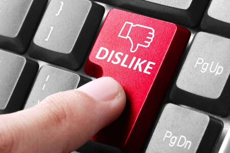 bad idea: Disliking something. gesture of finger pressing dislike button on a computer keyboard Stock Photo