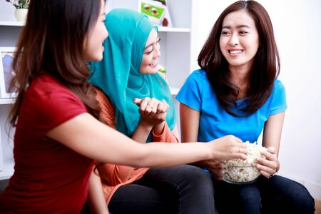 snack time: portrait of three beautiful women enjoying a bowl of popcorn