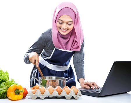 cooking ware: Young woman wearing hijab cooking with reference the laptop isolated on white background