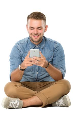 Portret van jonge man die op de vloer zit, met behulp van een mobiele telefoon, geïsoleerd. Klaar voor uw ontwerp Stockfoto