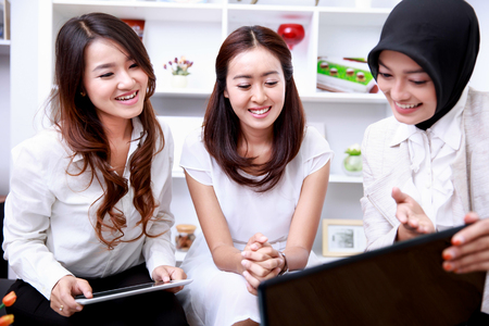 asian group: portrait of three young businesswomen talking about interesting project