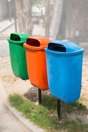 separacion de basura: Un retrato de tres bin basura en diferentes colores y propósito en un parque