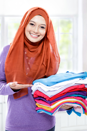 household tasks: portrait of young woman smiling and presenting clean clothes after ironing Stock Photo