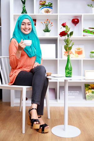 asian lady: full body portrait of attractive muslim woman sitting and drining a cup of tea at decorated living room