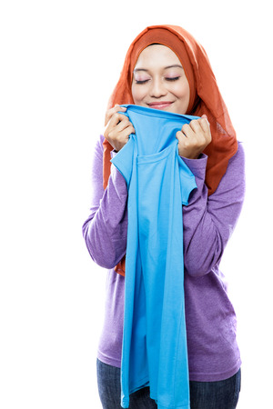houseclean: portrait of young woman wearing hijab holding and smelling the fresh clean laundry isolated on white