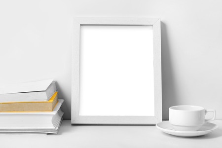 empty table: portait of white desk with blank photo frame, books, and coffee cup with white background