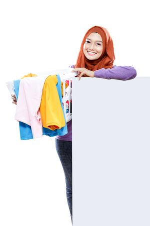 dirty clothes: portrait of beautiful housewife carrying laundry basket full of dirty clothes and laying on white board isolated on white