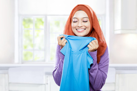 houseclean: portrait of young woman wearing hijab holding and smelling the fresh clean laundry Stock Photo
