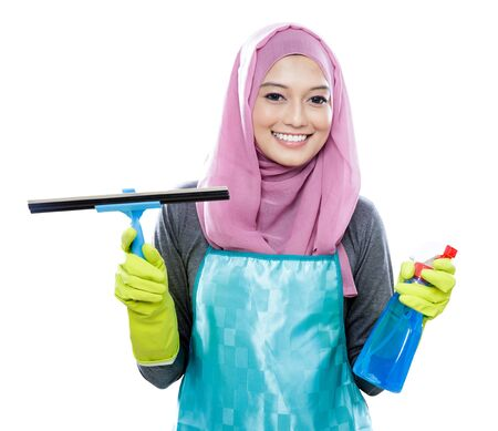 housewife gloves: portrait young woman wearing hijab holding squeegee and cleaning spray with copy space isolated on white