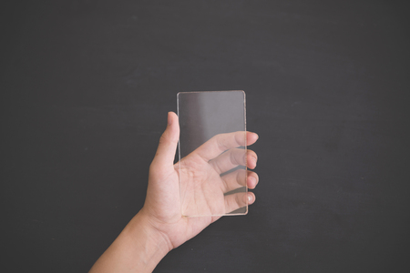hand phone: A portrait of a blank glass square on black background, futuristic transparent smart phone mock up Stock Photo
