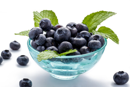 fruit background: a bowl of fresh blueberry with mint leaves on white background Stock Photo