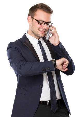 watch over: portrait of Businessman looking at his watch while speaking on the phone. isolated over white background