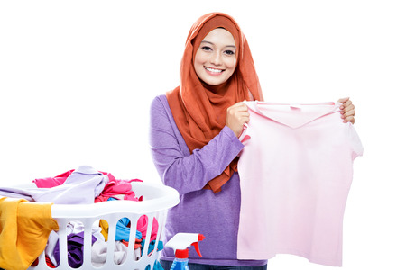 pick up: portrait of young woman wearing hijab ironing while pick up a clothes isolated on white
