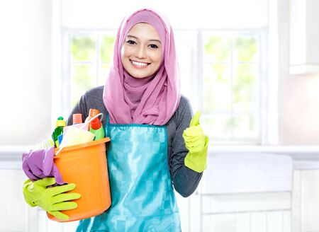 household: portrait of housewife wearing hijab holding bucket full of cleaning supplies and giving thumbs up with copy space