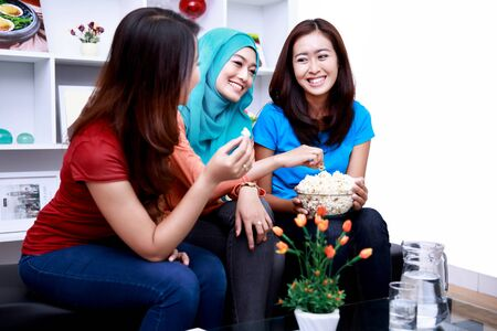 snacking: portrait of three women friends wnjoying time toghether while snacking a bowl of popcorn Stock Photo
