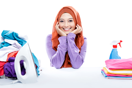 portrait of young smiling woman wearing hijab sitting between fresh clean laundry