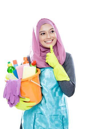 niña pensando: retrato de mujer joven con el pensamiento hijab mientras sostiene un cubo lleno de productos de limpieza aislados sobre fondo blanco
