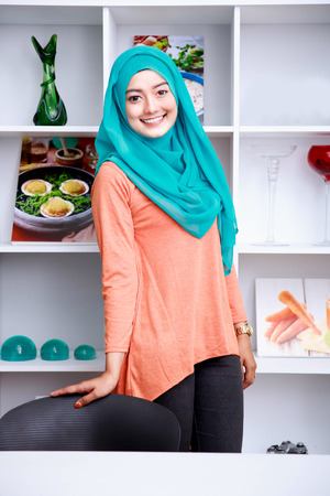 portrait of beautiful young woman wearing hijab standing with shelf and some ornaments at background