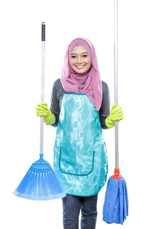 house maid: portrait of housewife wearing hijab holding broom and mop isolated on white