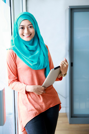 muslimah: portrait of beautiful muslim woman smiling while holding a tablet Stock Photo