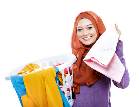 'pick up': portrait of housewife wearing hijab carrying laundry basket and pick up one clothes isolated on white