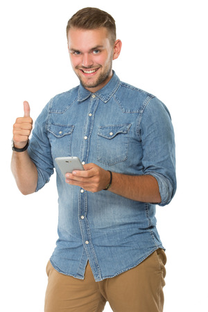 well build: portrait of young man holding a cellphone, thumb up, smiling. ready for your design Stock Photo