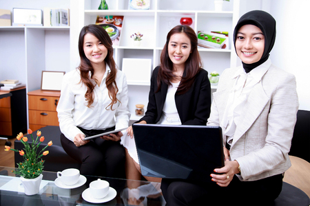 relation: portrait of three young businesswomen smiling while meeting