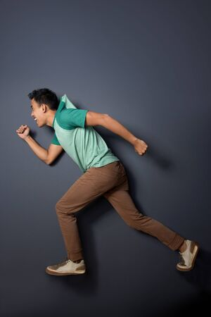 casual wear: portrait of young man running, his t-shirt being pulled something invicible, conceptual. ready for your design Stock Photo