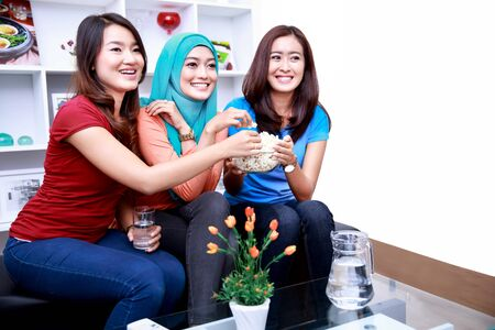 roommates: portrait of three women friends look excited watching a movie together and snacking a bowl of popcorn Stock Photo