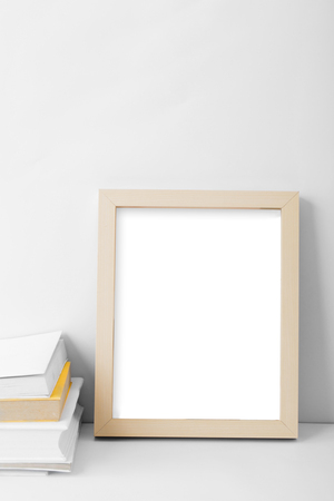 photo frame: portrait of desk blank photo frame nest to stack of books with copy space on white background