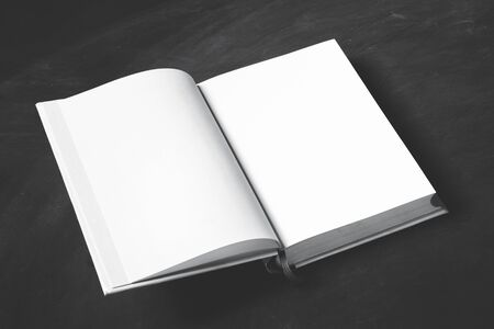 portrait of open thick book with blank page on black board for background