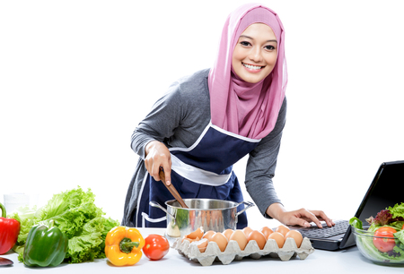 hijab: portrait of Young smiling woman wearing hijab cooking with reference the laptop isolated on white