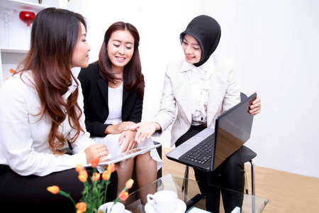 office presentation: portrait of a group of young businesswomen meeting at office living room