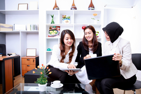portrait of three beautiful businesswomen meeting at office living room