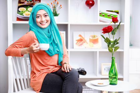 young asian: portrait of attractive muslim woman enjoying a cup of tea at decorated living room Stock Photo