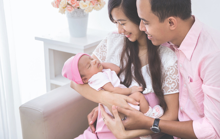asian baby: Couple looking at their sleeping baby girl, close up Stock Photo