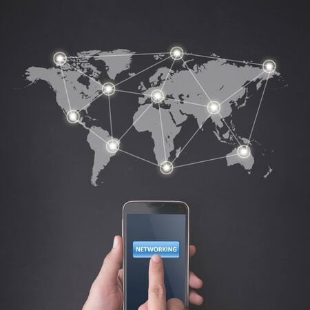 linking: Finger pressing global networking button on smartphone on chalkboard background