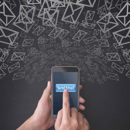 correo electronico: Dedo que presiona el botón enviar correo electrónico en el teléfono inteligente en el fondo de la pizarra