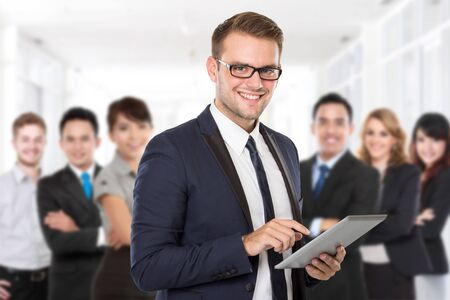 team from behind: Businessman with his team member behind. smiling with crossed arms Stock Photo