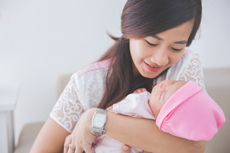 mother: Asian woman holding her sleeping baby girl, close up Stock Photo