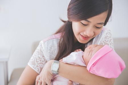 bebes niñas: Mujer asiática que sostiene a su bebé durmiente niña, de cerca Foto de archivo