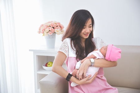 Asian woman holding her sleeping baby girl, close up Stock Photo