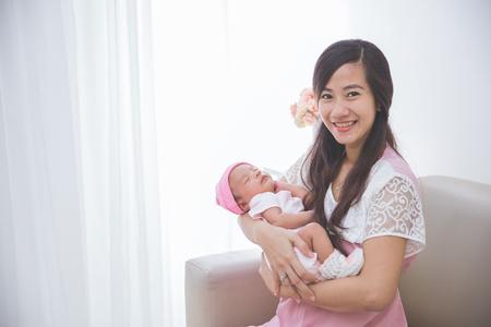 アジアの女性の彼女の眠っている女の赤ちゃんを保持