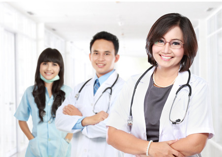 community health care: portrait of Smiling medical doctor with stethoscope with her staff.